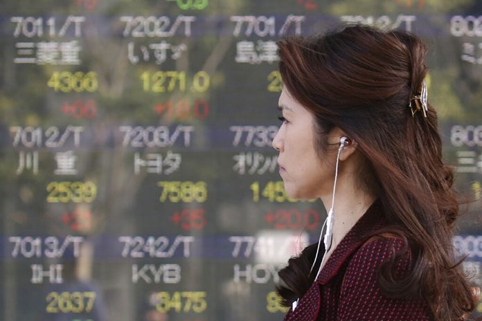A woman walks by an electronic stock board of a securities firm in Tokyo, Tuesday, Nov. 5, 2019. Asian shares have advanced after the Dow Jones Industrial Average returned to a record high. Benchmarks rose across the region, led by a 2% jump in Japan's Nikkei 225 index. (AP Photo/Koji Sasahara)