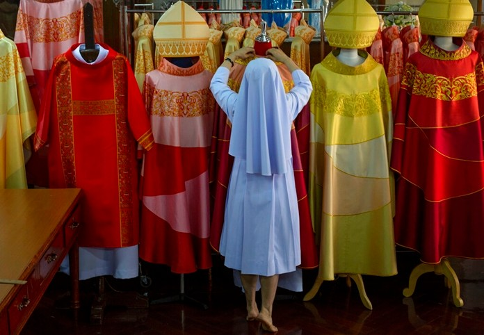 Sister Sukanya Sukchai adjusts a newly made chasubles at Catholic preparatory school in Bangkok, Thailand Friday, Nov. 8, 2019. (AP Photo/Gemunu Amarasinghe)