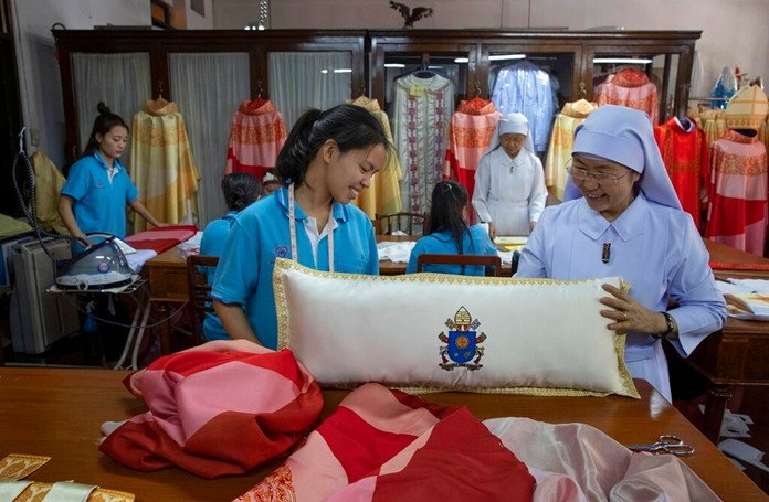 Sister Sukanya Sukchai, right, inspects a newly made pillow at a Catholic preparatory school in Bangkok, Thailand Friday, Nov. 8, 2019. (AP Photo/Gemunu Amarasinghe)