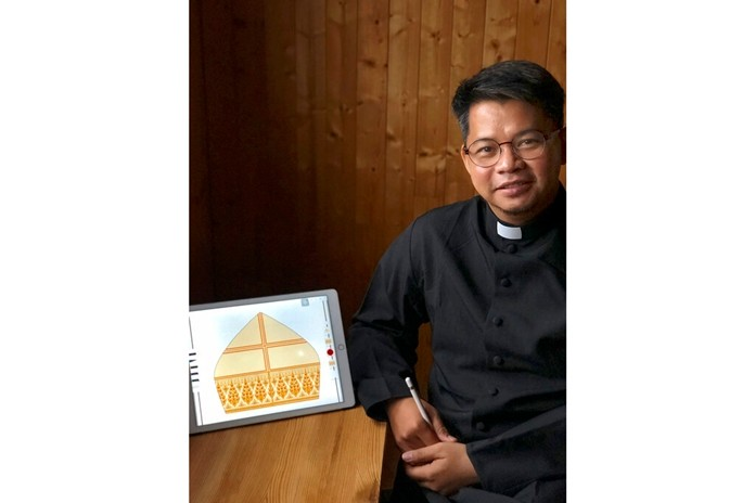 This Friday, Nov. 1, 2019, photo provided by Rev. Naruenat Pankrod shows Pankrod with a design he created for Pope Francis miter for his four-day visit to Thailand, at San Giorgio delle Pertiche in Veneto, Italy. Rev. Pankrod said by phone from Italy that he worried the kranok might be too elaborate for a pontiff who favors simplicity, but it's received the seal of approval. (Naruenat Pankrod via AP)