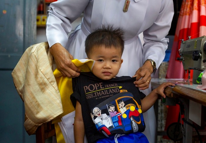 A boy wears a T-shirt marking Pope Francis' visit to Thailand at a Catholic preparatory school in Bangkok, Thailand Friday, Nov. 8, 2019. (AP Photo/Gemunu Amarasinghe)