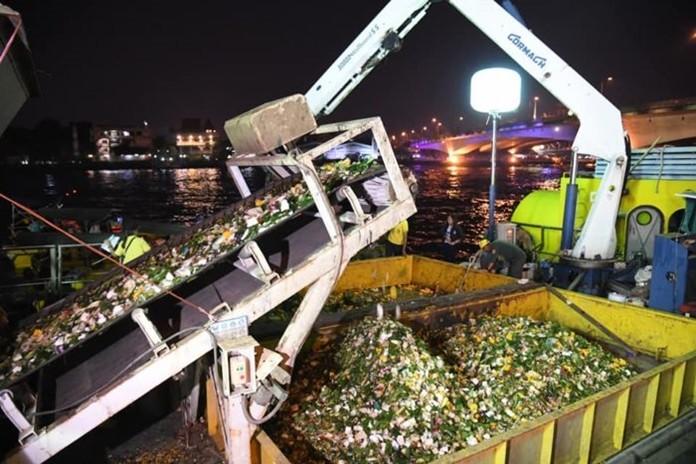 City workers work swiftly through the night collecting krathongs from Bangkok's waterways.