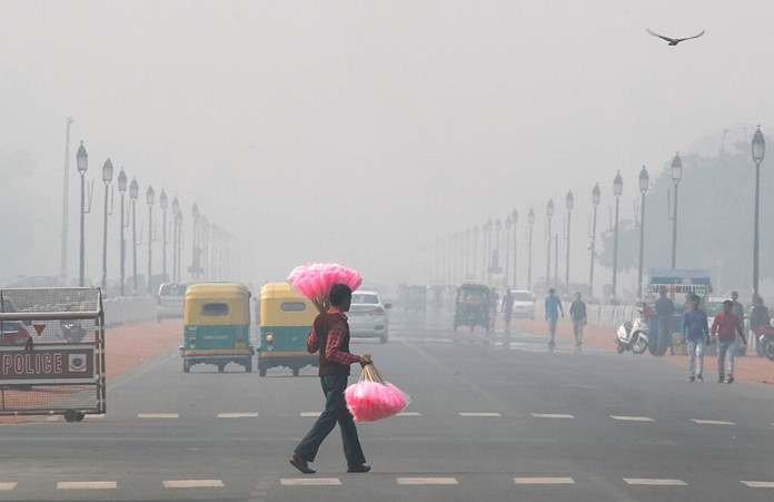 A sweet candy vendor walks amidst thick layer of smog as he looks for customers in New Delhi, India, Tuesday, Nov. 12, 2019. (AP Photo/Manish Swarup)