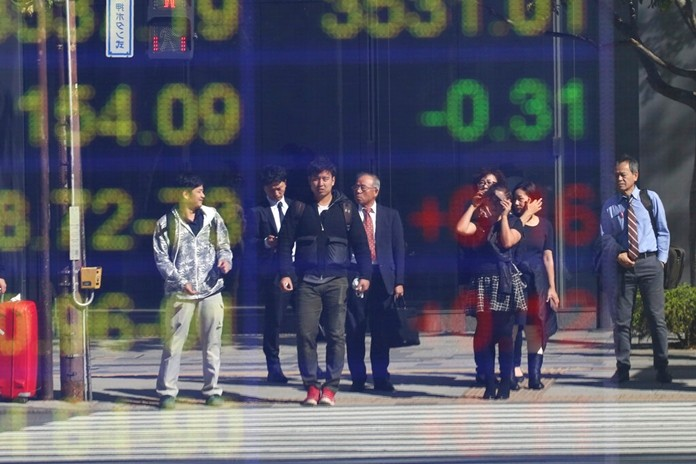 People are reflected on the electronic board of a securities firm in Tokyo, Tuesday, Nov. 5, 2019. Asian shares have advanced after the Dow Jones Industrial Average returned to a record high. Benchmarks rose across the region, led by a 2% jump in Japan's Nikkei 225 index. (AP Photo/Koji Sasahara)