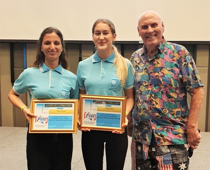 MC Ron Dittmer poses with Linda Heil and Sarah Chagri after presenting them with the PCEC's Certificate of Appreciation for their presentation on their volunteer service for Pattaya's Health and Human Network Foundation Thailand.