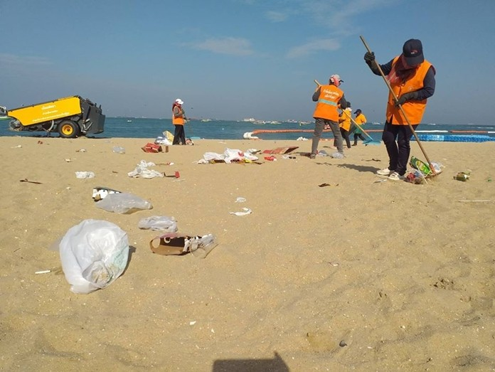 People spread out across the beach, picking up plastic bags, food containers and krathongs that washed back to shore Nov. 12.