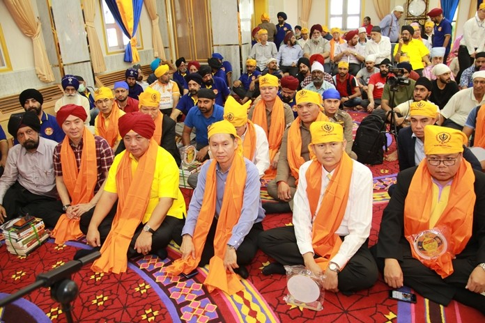 The minister together with city fathers and high-ranking government officials join the Sikh congregation in prayer and meditation.