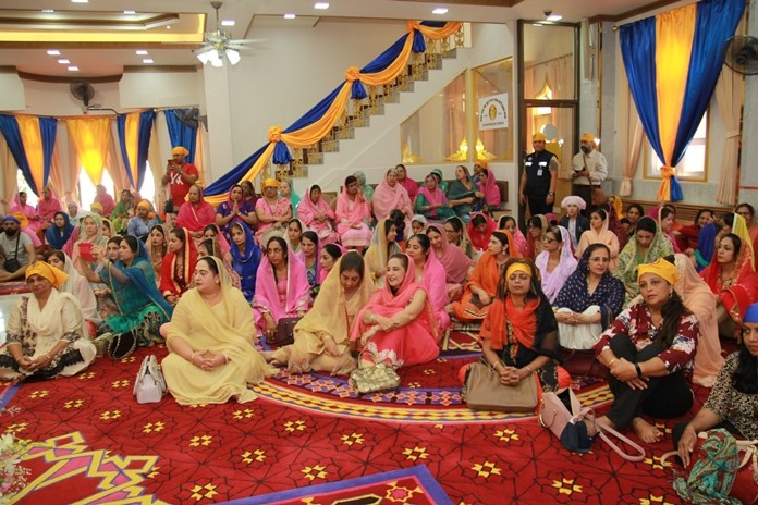 The Sikh lady's congregation await the arrival of the dignitaries.
