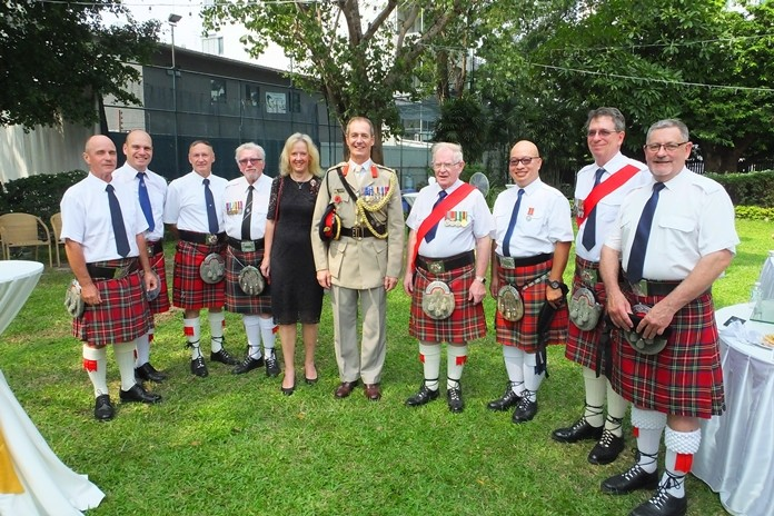 Colonel Roger and Kimberley Lewis stand with members of The British Club Pipes and Drums band.