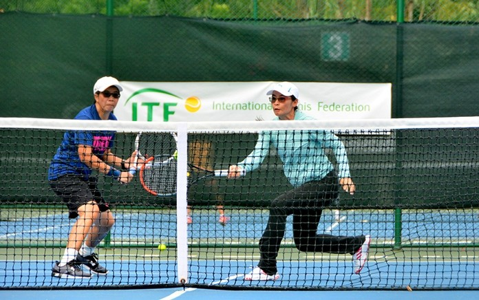 Women's Doubles 35+ tennis players Arunya Wongkaew and Puttaruksa Jantamad return a volley during the ITF Seniors Championship held at Royal Cliff Royal Cliff Beach Resort's Fitz Club.
