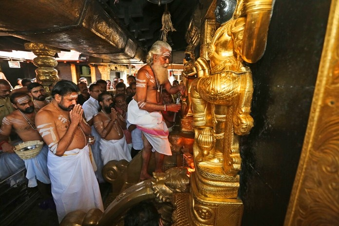 In this Nov. 5, 2018, file photo, the head priest opens the sanctum sanctorum of the Sabarimala temple, one of the world's largest Hindu pilgrimage sites, in Kerala state, India. (AP Photo/Manish Swarup, File)