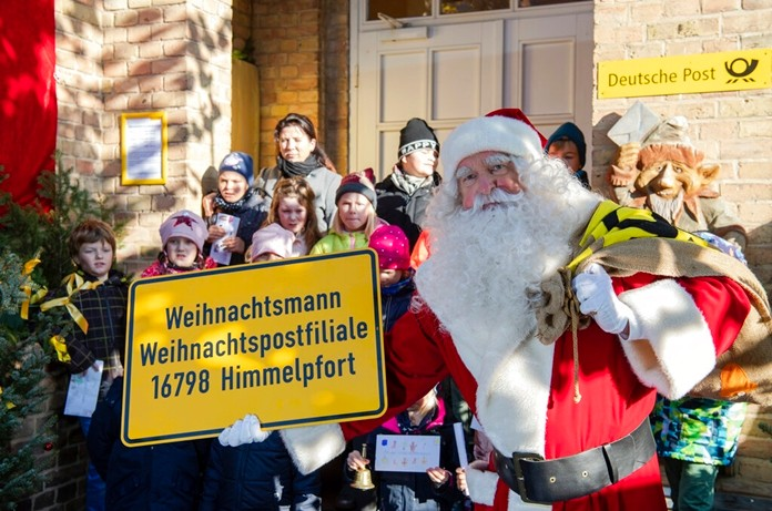 A man dressed as Santa Claus is welcomed by children during the opening of the most famous German Christmas mail office in the small village of Himmelpfort (Heaven's Door) north of Berlin, Germany, Thursday, Nov. 14, 2019. (Soeren Stache/dpa via AP)