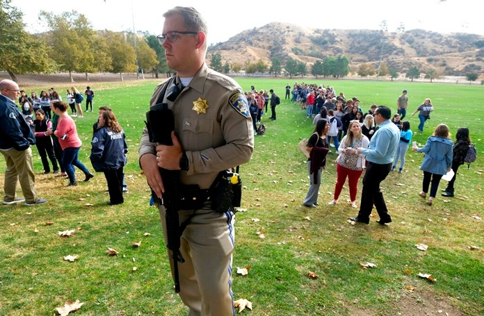 A police officer stands guard as students wait to reunite with their parents following a shooting at Saugus High School that injured several people, Thursday, Nov. 14, 2019, in Santa Clarita, Calif. (AP Photo/Ringo H.W. Chiu)
