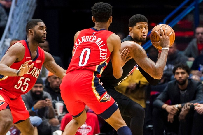 Los Angeles Clippers forward Paul George, right, keeps the ball away from New Orleans Pelicans guards E'Twaun Moore (55) and Nickeil Alexander-Walker (0) in the second half of an NBA basketball game in New Orleans, Thursday, Nov. 14, 2019. (AP Photo/Sophia Germer)