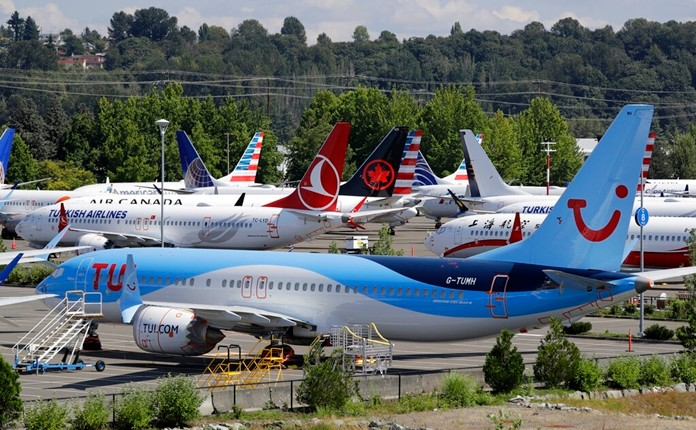 This Aug. 15, 2019, file photo shows dozens of grounded Boeing 737 MAX airplanes crowd a parking area adjacent to Boeing Field in Seattle. Boeing is settling more of the roughly 150 lawsuits filed by families of passengers killed in two crashes of the 737 Max jet. A Seattle law firm said Friday, Nov. 15, 2019, it settled four cases involving passengers on the Lion Air Max that crashed off the coast of Indonesia in October 2018. On Thursday, a judge approved settlements of nine other cases.(AP Photo/Elaine Thompson, File)