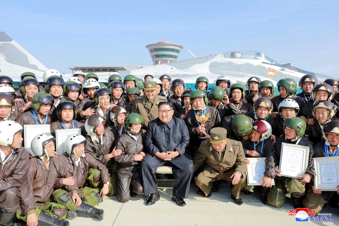 """In this undated photo provided on Saturday, Nov. 16, 2019 by the North Korean government, North Korean leader Kim Jong Un, front center, poses with pilots during his inspection of a flight demonstration of military aircraft at an airfield in North Korea. Independent journalists were not given access to cover the event depicted in this image distributed by the North Korean government. The content of this image is as provided and cannot be independently verified. Korean language watermark on image as provided by source reads: """"KCNA"""" which is the abbreviation for Korean Central News Agency. (Korean Central News Agency/Korea News Service via AP)"""