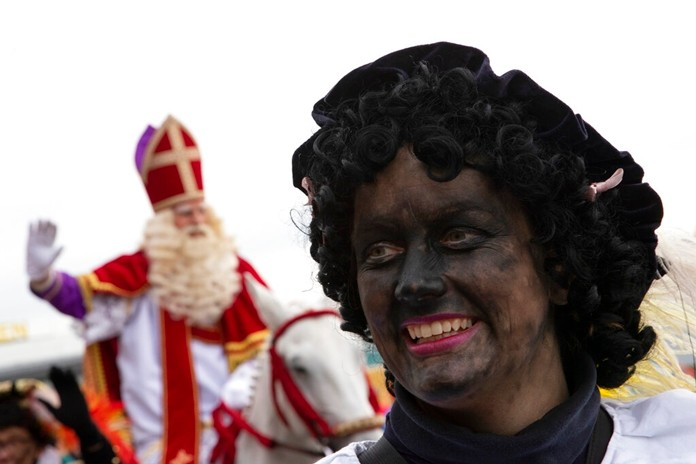 Zwarte Piet, or Black Pete, the blackfaced sidekick of Saint Nicholas, rear, walks in a parade in Scheveningen harbor, near The Hague, Netherlands, Saturday, Nov. 16, 2019. (AP Photo/Peter Dejong)