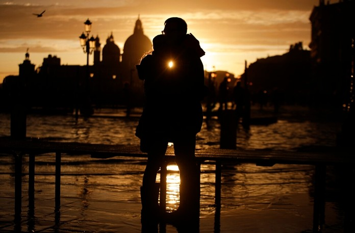 A couple stands in a golden sunset in Venice on Sunday, just hours after an exceptional 1.5 meter tide receded from nearby St. Mark's Square. It was the third flood topping 1.5 meters this week, following Tuesday's 1.87-meter flood which was the worst in 53 years. (AP Photo/Luca Bruno)