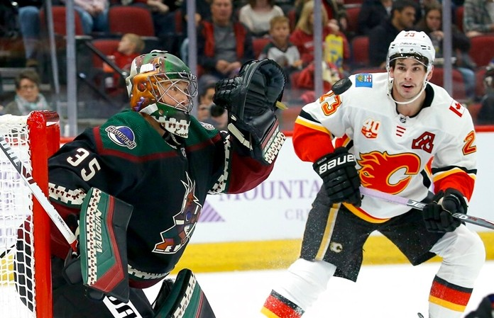 Arizona Coyotes goaltender Darcy Kuemper (35) reaches out to make a glove save on a shot as Calgary Flames center Sean Monahan (23) looks on during the first period of an NHL hockey game, Saturday, Nov. 16, 2019, in Glendale, Ariz. (AP Photo/Ross D. Franklin)