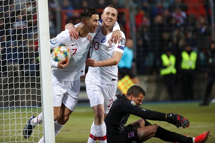 Portugal's Cristiano Ronaldo, left, celebrates with his teammate Diogo Jota after he scored his side's second goal during the Euro 2020 group B qualifying soccer match between Luxembourg and Portugal at the Josy Barthel stadium in Luxembourg, Sunday, Nov. 17, 2019. (AP Photo/Francisco Seco)