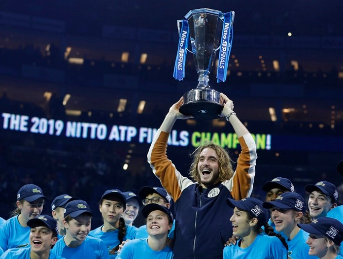 Stefanos Tsitsipas of Greece holds up the trophy and celebrates with the ball kids after defeating Austria's Dominic Thiem in the final of the ATP World Finals tennis match at the O2 arena in London, Sunday, Nov. 17, 2019. (AP Photo/Kirsty Wigglesworth)