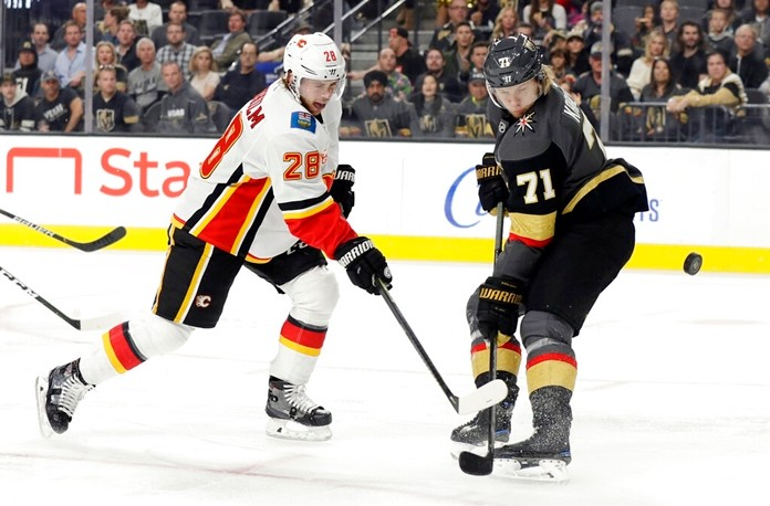 Vegas Golden Knights center William Karlsson (71) defends as Calgary Flames center Elias Lindholm (28) shoots during the first period of an NHL hockey game Sunday, Nov. 17, 2019, in Las Vegas. (AP Photo/Isaac Brekken)