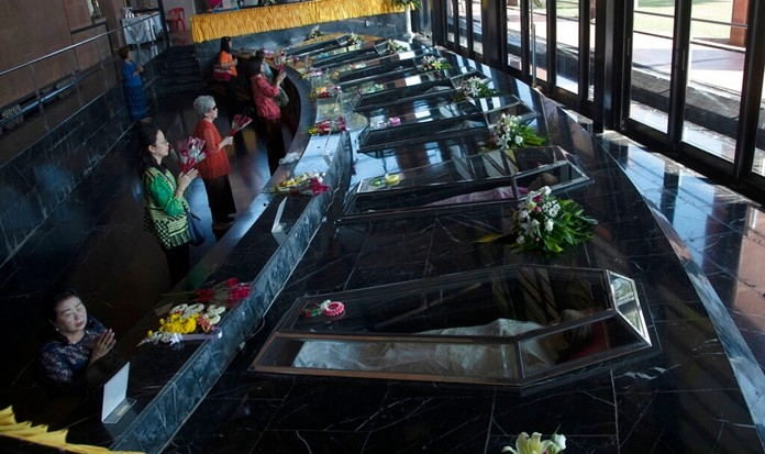 Catholic devotees pray in front of glass caskets containing the seven replicas of the Blessed Martyrs at Christ Church, Songkhon village in Mukdahan province, northeastern Thailand Saturday, Oct. 19, 2019. (AP Photo/Sakchai Lalit)