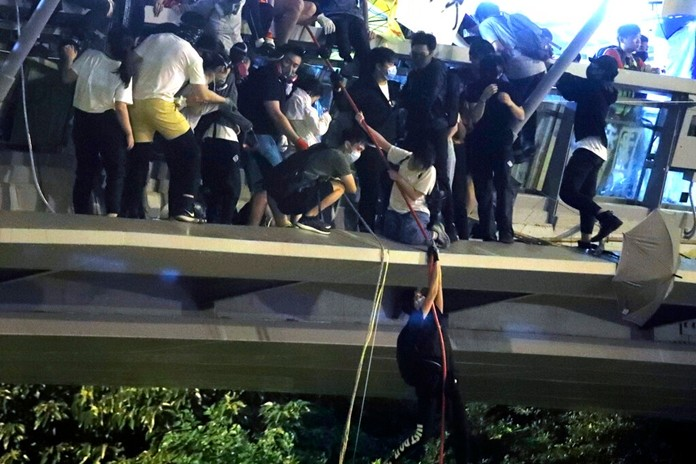 Protestors use a rope to lower themselves from a pedestrian bridge to waiting motorbikes in order to escape from Hong Kong Polytechnic University and the police in Hong Kong, Monday, Nov. 18, 2019. (AP Photo/Kin Cheung)