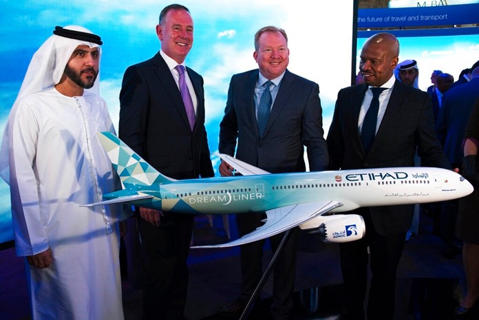 Etihad COO Mohammad al-Bulooki, left, Etihad CEO Tony Douglas, second left, Boeing Commercial Airplanes president and CEO Stanley A. Deal, third left, and Boeing Global Services President and CEO Ted Colbert, right, pose in front of a Boeing 787 Dreamliner model at the Dubai Airshow in Dubai, United Arab Emirates, Monday, Nov. 18, 2019. (AP Photo/Jon Gambrell)