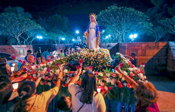 In this Friday, Oct. 18, 2019, photo, Catholic worshippers lay flowers at the base of a Mother Mary statue at the Christ Church in Songkhon village, Mukdahan province, northeastern of Thailand. (AP Photo/Sakchai Lalit)
