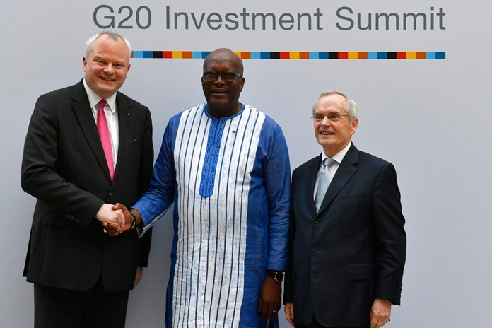 """Stefan Liebing, left, chairman of the German'African Business Association (Afrika-Verein der deutschen Wirtschaft), and Heinz-Walter Grosse, right, chairman of the Sub-Saharan Africa Initiative of German Business (SAFRI), pose with Burkina Faso's President Roch Marc Christian Kabore, center, as he arrives to attend the """"G20 Investment Summit - German Business and the CwA Countries 2019"""" on the sidelines of a Compact with Africa (CwA) in Berlin on November 19, 2019. (John MacDougall/Pool via AP)"""