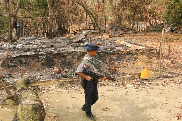 In this Sept. 6, 2017, file photo, a Myanmar security officer walks past burned Rohingya houses in Ka Nyin Tan village of suburb Maungdaw, northern Rakhine state of western Myanmar. (AP Photo, File)