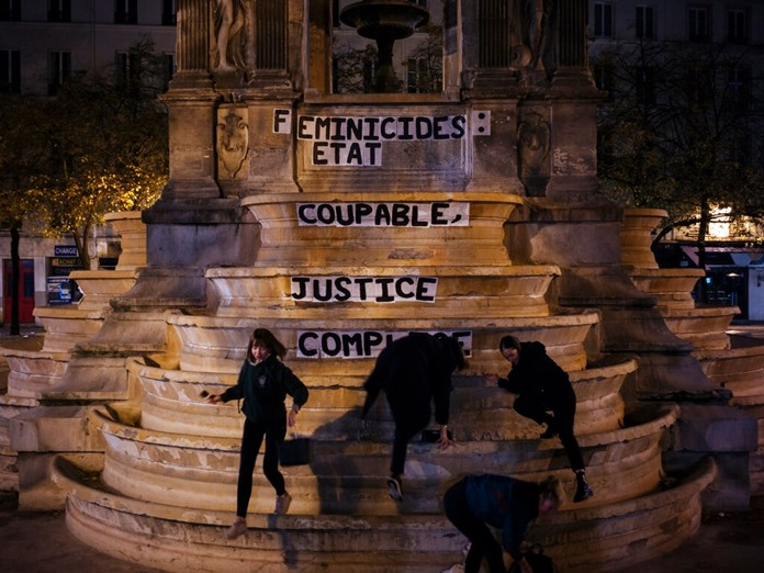 """In this photo taken in the early hours of Monday Nov. 4, 2019, from left to right, Pauline, Clivia, France and Lea paste a slogan on a fountain reading """" Femicides : guilty state, accomplice justice"""" in central Paris. (AP Photo/Kamil Zihnioglu)"""
