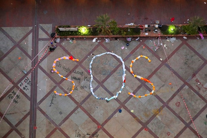"""An """"SOS"""" sign formed with clothes and helmets by protesters is seen inside the Hong Kong Polytechnic University campus in Hong Kong, Friday, Nov. 22, 2019. (AP Photo/Kin Cheung)"""
