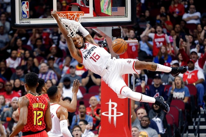 Houston Rockets guard Ben McLemore (16) hangs on the rim after his dunk as Atlanta Hawks forward De'Andre Hunter (12) looks on during the first half of an NBA basketball game, Saturday, Nov. 30, 2019, in Houston. (AP Photo/Michael Wyke)