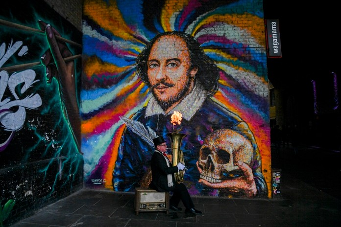 A man plays a trombone as a flame comes out of it, to entertain passersby, backdropped by a mural depicting playwright William Shakespeare, near to London Bridge, as the road are being progressively reopened in the aftermath of a terror attack, in London, Sunday, Dec. 1, 2019. Life is returning to normal in London after a man wearing a fake suicide vest went on a knife rampage killing two people and wounding others before being shot dead by police on Friday.(AP Photo/Alberto Pezzali)