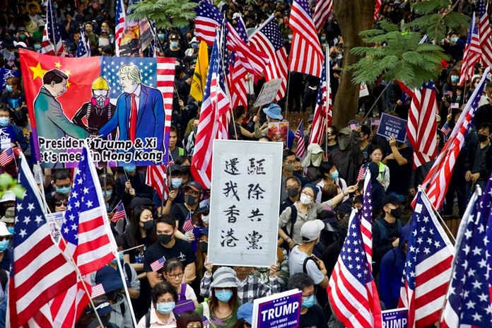 """Protesters hold banners and American flags during a rally outside the U.S. Consulate in Hong Kong, Sunday, Dec. 1, 2019. The banner at center reads """"Kick out communist, return Hong Kong."""" (AP Photo/Ng Han Guan)"""