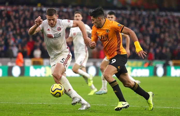 Sheffield United's Jack O'Connell, left, and Wolverhampton Wanderers's Raul Jimenez battle for the ball during the English Premier League soccer match at Molineux, Wolverhampton, England, Sunday Dec. 1, 2019. (Bradley Collyer/PA via AP)