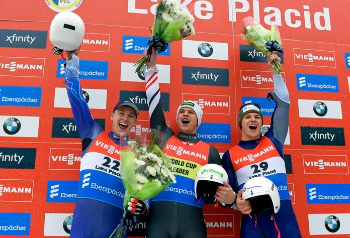From left, Tucker West, of the United States, Jonas Müller, of Austria, and Kevin Fischnaller, of Italy, celebrate after a men's World Cup luge event in Lake Placid, N.Y., on Sunday, Dec. 1, 2019. Müller finished first, West second, and Fischnaller third. (AP Photo/Hans Pennink)