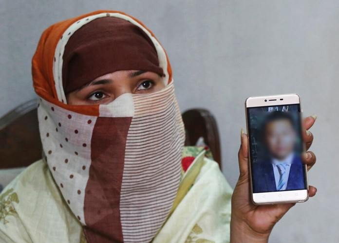 In this May 22, 2019 file photo, Sumaira a Pakistani woman, shows a picture of her Chinese husband in Gujranwala, Pakistan. Sumaira, who didn't want her full name used, was raped repeatedly by Chinese men at a house in Islamabad where she was brought to stay after her brothers arranged her marriage to the older Chinese man. (AP Photo/K.M. Chaudary, File)