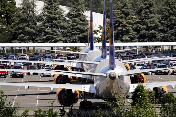 In this Thursday, Aug. 15, 2019, file photo, three grounded Boeing 737 Max airplanes, built for Icelandair, sit parked in a lot normally used for cars in an area adjacent to Boeing Field, in Seattle. (AP Photo/Elaine Thompson, File)