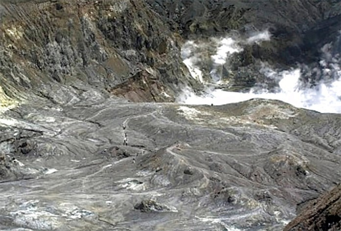 In this image released by GeoNet, tourists can be seen on a trail near the volcano's crater Monday, Dec. 9, 2019, on White Island, New Zealand. (GNS Science via AP)