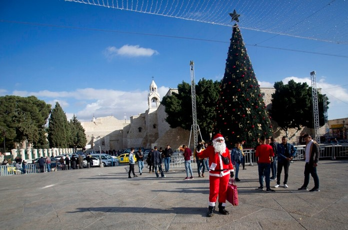 In this Thursday, Dec. 5, 2019, photo, a Palestinian wearing a Santa Claus costumes welcomes Christian visitors outside the Church of the Nativity, traditionally believed by Christians to be the birthplace of Jesus Christ, in the West Bank city of Bethlehem. (AP Photo/Majdi Mohammed)