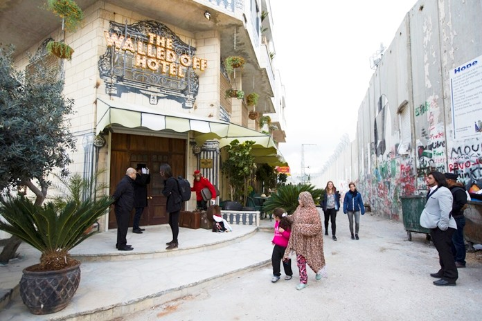 """In this Friday, March 3, 2017 file photo, People pass by the """"The Walled Off Hotel"""" and the Israeli security barrier the West Bank city of Bethlehem. (AP Photo/Dusan Vranic, File)"""