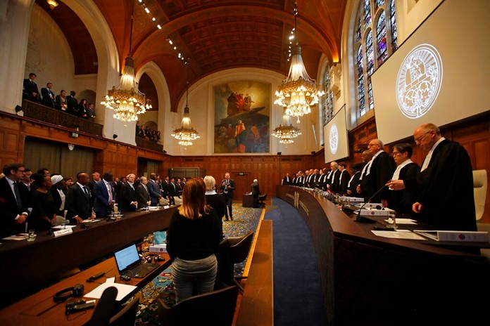 People stand in the court room of the International Court of Justice in The Hague, Netherlands, Tuesday, Dec. 10, 2019 as the U.N.'s highest court begins a hearing into allegations of genocide in Myanmar over the military campaign against the Rohingya minority. (AP Photo/Peter Dejong)