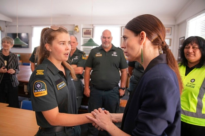New Zealand's Prime Minister Jacinda Ardern, right, talks with first responders in Whakatane, New Zealand, Tuesday, Dec. 10, 2019. (Dom Thomas/Pool Photo via AP)