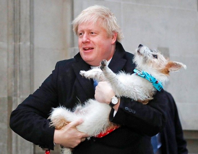 Britain's Prime Minister and Conservative Party leader Boris Johnson holds his dog Dilyn as he leaves after voting in the general election at Methodist Central Hall, Westminster, London, Thursday, Dec. 12, 2019. (AP Photo/Frank Augstein)