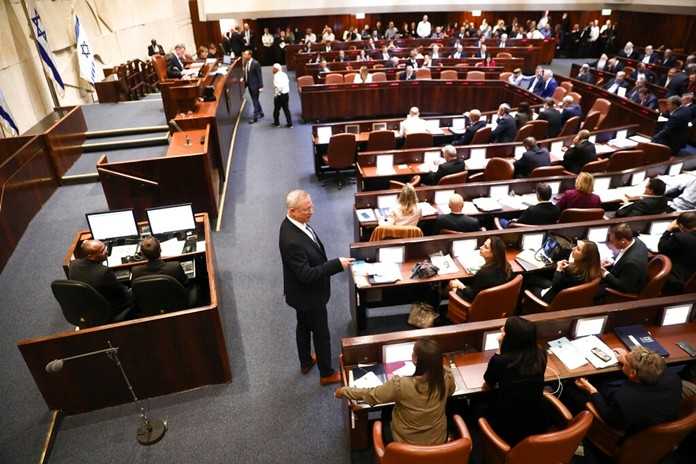 Blue and White party leader Benny Gantz, center, stands during a Knesset session in Jerusalem, Wednesday, Dec. 11, 2019. (AP Photo/Oded Balilty)