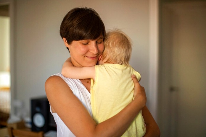 In this photo taken on Wednesday, June 19, 2019, Clara Massons holds her two years old son Jaume at her home in Barcelona, Spain. (AP Photo/Emilio Morenatti)
