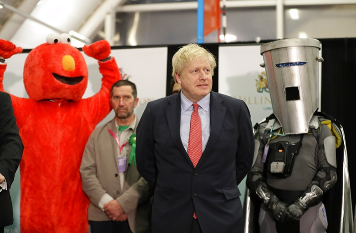 Bobby Smith, a political and fathers' rights activist and founder and leader of the 'Give Me Back Elmo' party, left, and Independent candidate Count Binface stand either side of Britain's Prime Minister and Conservative Party leader Boris Johnson wait for the Uxbridge and South Ruislip constituency count declaration at Brunel University in Uxbridge, London, Friday, Dec. 13, 2019. (AP Photo/Kirsty Wigglesworth)